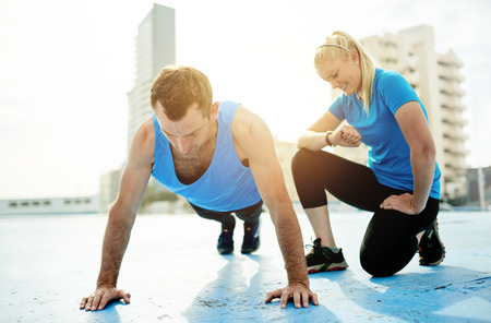 strengthening: Smiling young woman timing a man doing pushups while exercising together outside on a beachside promenade on a sunny day