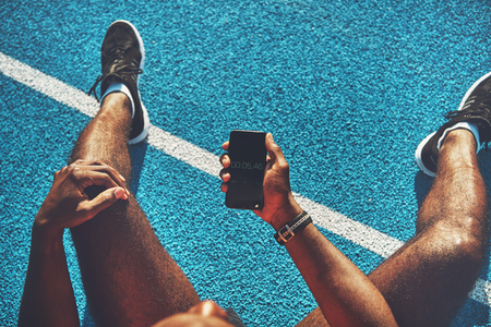 Young African male athlete in sportswear sitting alone on the lanes of a running track checking his running time on his smartphone