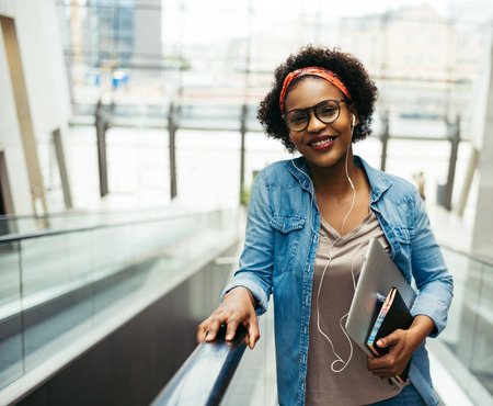 Young African female entrepreneur smiling confidently while riding up an escalator in the lobby of a modern office building carrying a laptop and wearing earphones