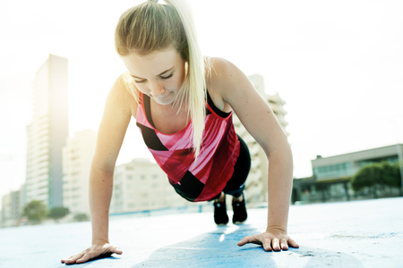 strengthening: Focused young blonde woman in sportswear doing pushups while exercising alone outside in the city on a sunny day