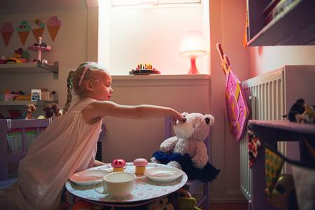 La muchacha da té a su oso mientras que juega la fiesta del té. Tiro horizontal en el interior. Foto de archivo - 83585881