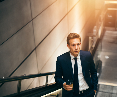 go inside: Young businessman in a suit drinking a coffee and riding up an escalator in a subway station during his morning commute