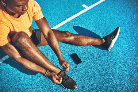 Focused young African male athlete in sportswear sitting alone on the lanes of a running track tying up his shoes before training Stock Photo