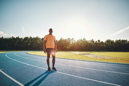 Focused young African male athlete in sportswear standing alone on a runnng track mentally preparing for a race Stock Photo