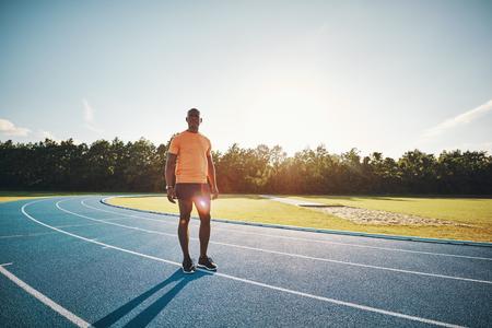 Geconcentreerde jonge Afrikaanse mannelijke atleet in sportkleding die zich alleen op een runnngspoor bevinden die zich psychologisch op een race voorbereiden Stockfoto