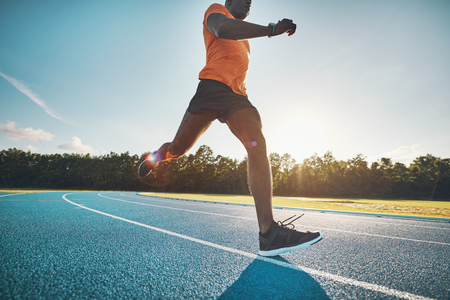 Focused young African male athlete in sportswear sprinting alone down a running track on a sunny day Stock Photo