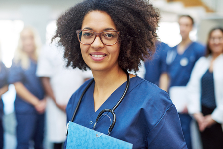 Young black female doctor looking at camera in a hospital standing in front of medical team