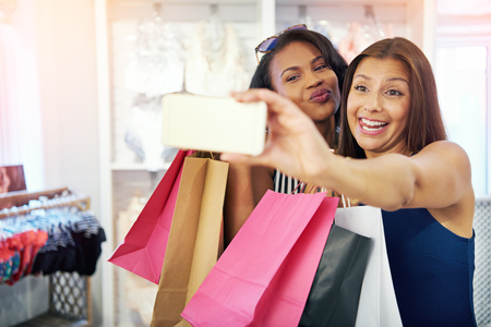 Playful young women shoppers posing for a selfie in the store with their colorful designer bags
