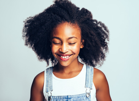 Smiling young African girl with long curly hair and wearing dungarees standing with her eyes closed against a gray background Stock Photo