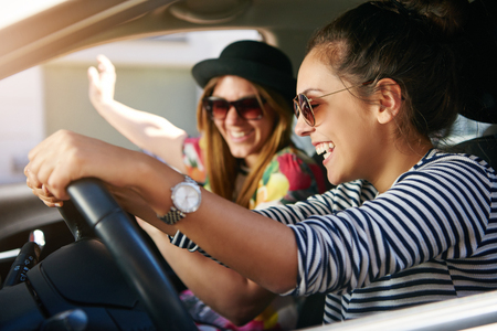 Two attractive young friends wearing sunglasses laughing together while driving in a car through the city on a sunny day
