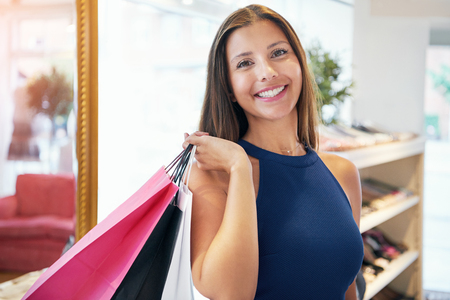 mirror: Female shopper in sleeveless blue dress holding pink, black and white paper shopping bags over her shoulder in store. Includes copy space.