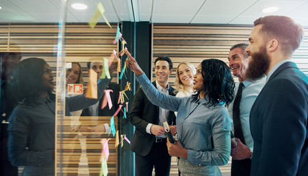 Happy creative businesspeople brainstorming in office, placing sticky notes with ideas on glass Foto de archivo