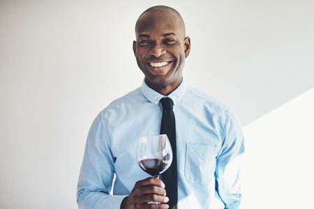 Mature African businessman in a shirt and tie smiling while drinking a glass of red wine Stock Photo