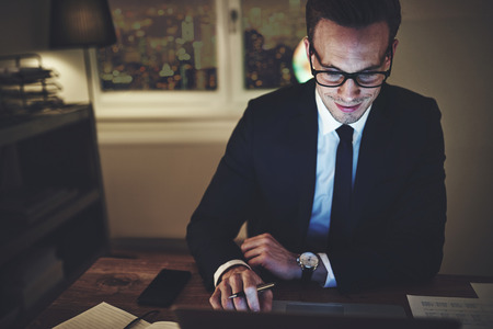 Smiling businessman working on laptop at night sitting in office looking concentrated 版權商用圖片