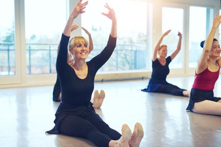 大人の女性のクラスでバレエ体操をしながら手で床に座ってにこにこしています。