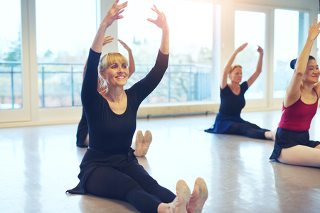 Smiling adult women sitting on floor with hands up while doing ballet gymnastics in the class.