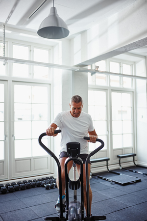 Determined mature man in sportswear pushing himself riding a stationary bike while working out alone at the gym Stock Photo