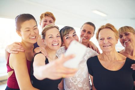 Groupe d'âge mixte de femmes qui rient debout bras dessus bras dessous prenant un selfie dans un studio de danse Banque d'images - 84340160