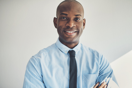 Confident African businessman wearing a shirt and tie standing with his arms crossed in his home office