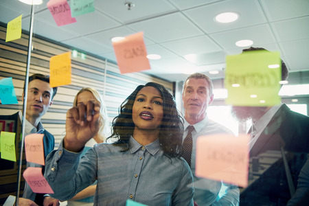 Group of businesspeople brainstorming with woman in foreground, putting sticky note on glass 스톡 콘텐츠