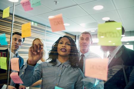 Groupe de gens d'affaires qui remue-méninges avec la femme au premier plan, mettant une note collante sur le verre Banque d'images - 84414363