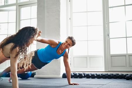 Twee glimlachende jonge vrouwelijke vrienden in sportkleding die opdrukoefeningen en hoge fiving samen op de vloer van een gymnastiek doen