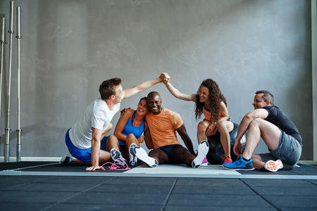 Two friends in sportswear high fiving each other while sitting on the floor of a gym talking with friends after a workout