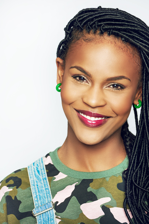 Stylish young African-American woman in casual military clothes looking at camera.