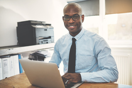 Smiling African businessman wearing glasses sitting at a desk working online with a laptop in his home office Stock Photo
