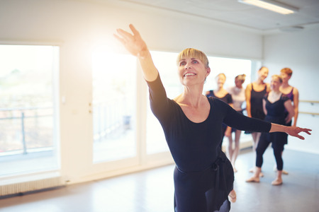 Cheerful woman performing a ballet dance in adult group in class.