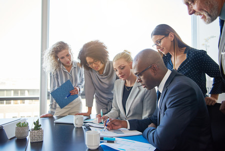 Group of focused diverse businesspeople smiling and working together around a boardroom table reviewing charts and paperwork Stock Photo