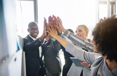 Diverse group of smiling work colleagues high fiving each other while standing together in a bright modern office