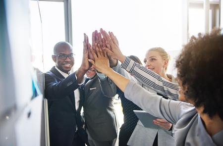 밝은 현대적인 사무실에서 함께 서있는 동안 서로를 높이 들고 웃는 직장 동료의 다양한 그룹 스톡 콘텐츠