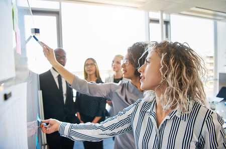 Group of focused business colleagues brainstorming together on a whiteboard during a strategy session in a bright modern office Imagens - 84414390