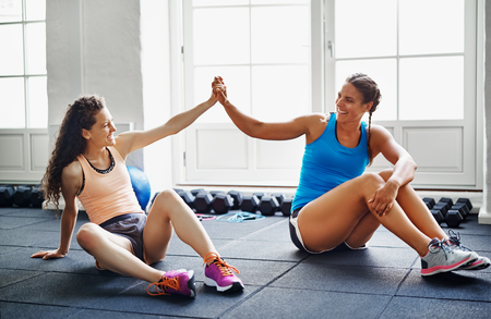 Two smiling young female friends in sportswear sitting together on the floor of a gym high fiving each other