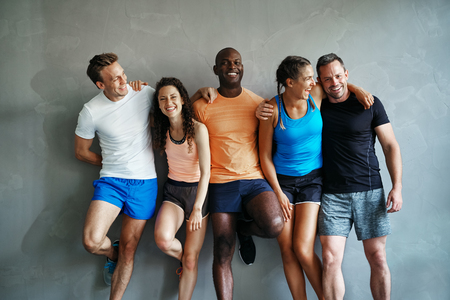 Smiling group of friends in sportswear laughing together while standing arm in arm in a gym after a workout Stock fotó