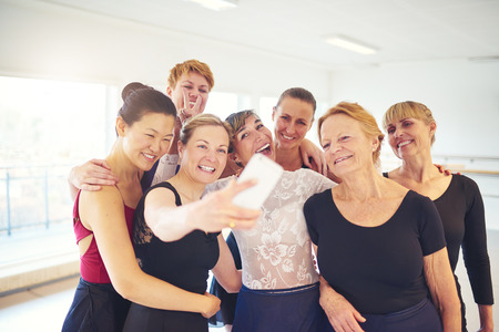 Mixed age group of women laughing while standing arm in arm together taking a selfie during ballet class