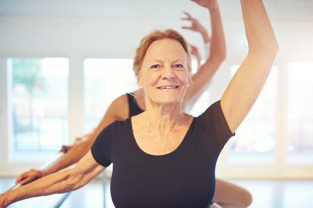 Senior female balletdancer standing with hand up and looking at camera while doing exercise in class.