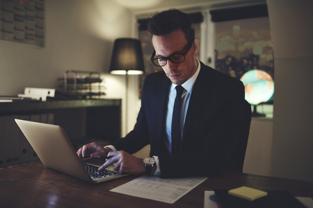 Businessman working concentrated on documents at night, working overtime at office 版權商用圖片 - 84396215