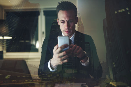The intelligent accountant sitting in the office and surfing the smartphone at night.