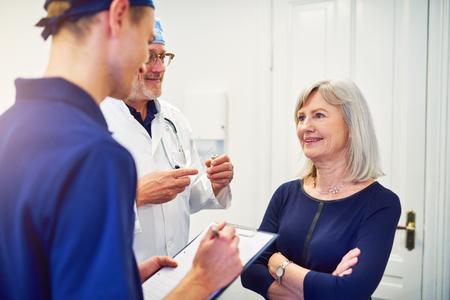 Volwassen dokter die rijpe vrouwelijke patiënt raadplegen terwijl jonge medewerker die en zich in tablet bevinden schrijven. Stockfoto