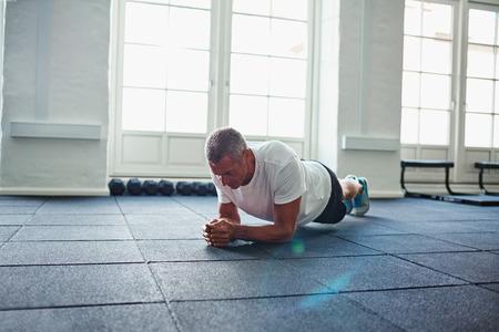 Fokussierter reifer Mann in der Sportkleidung, die alleine auf dem Boden beim in einer Turnhalle allein ausarbeiten planking ist Standard-Bild - 84707669