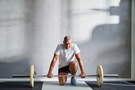 Focused senior man in sportswear kneeling alone in a gym preparing to lifting weights during a workout Stock Photo