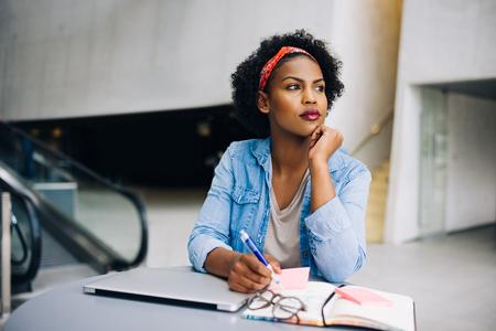 현대 사무실 건물 로비에서 테이블에 작업하는 동안 생각 깊은 젊은 아프리카 여성 기업인 초점을 맞추고