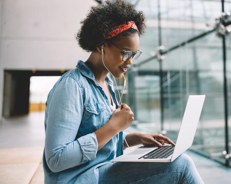 Enfocado a joven estudiante universitario africano trabajando en una computadora portátil mientras está sentado en un banco en el campus preparando para un examen Foto de archivo