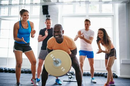 Grupo diverso de jóvenes animando a su amigo masculino levantando pesas en un gimnasio mientras hacía ejercicio en un gimnasio Foto de archivo