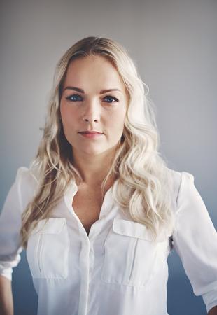 Portret van een zelfverzekerde jonge zakenvrouw staan voor een kantoormuur met haar handen op haar heupen
