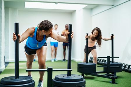 두 웃 고 백그라운드에서 친구와 함께 체육관에서 무게를 밀고 운동복에 맞는 젊은 여성