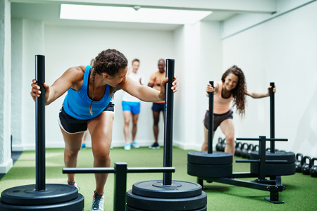Two fit young women in sportswear smiling and pushing weights in a gym with friends in the background