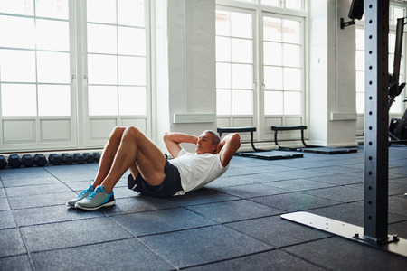 Senior man in sportswear doing sit ups alone while working out on the floor of a gym
